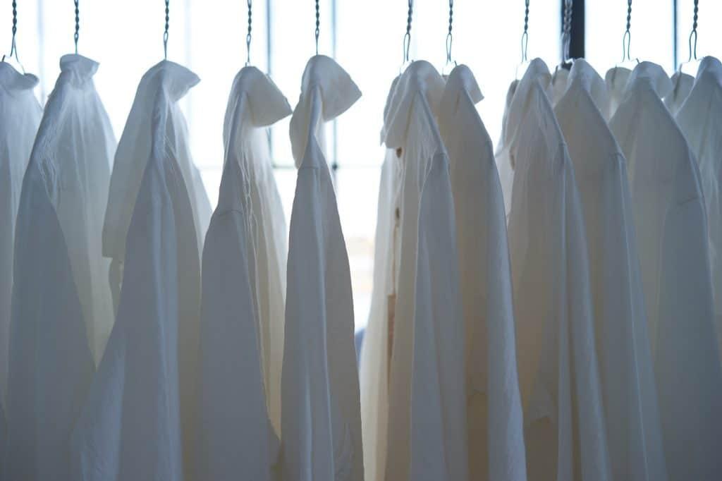 Viele weiße Hemden hängen in einer Reihe auf Drahtbügeln