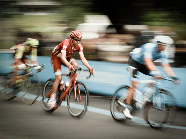 drei Radfahrer während eines Wettkampfes, der mittlere im Fokus.