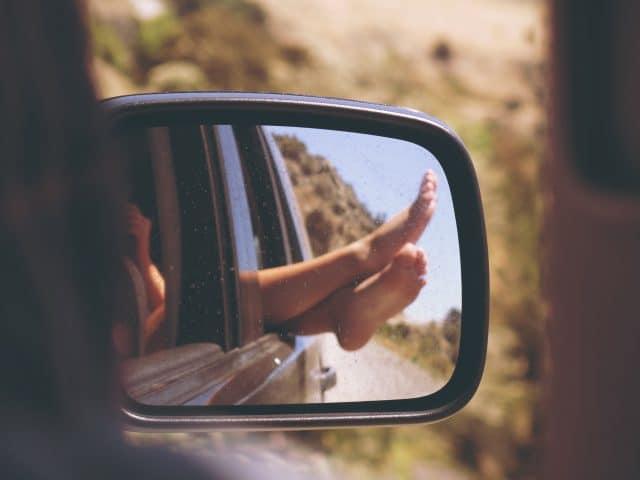 Ein Autospielgel, in dem nackte Füße zu sehen sind, die aus dem Autofenster hängen