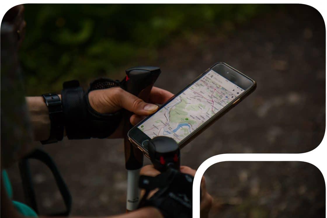 Mobiltelefon mit geöffneter Karte in dein Händen eines Wanderers im Wald
