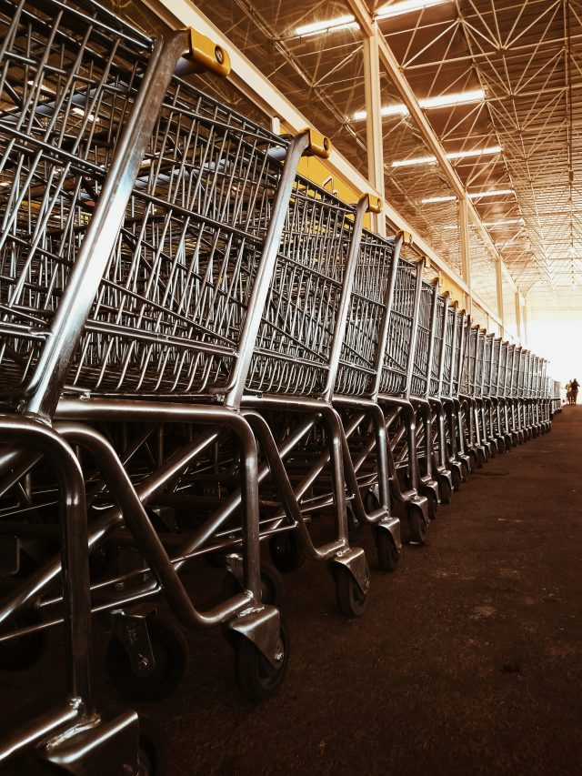 eine lange Reihe Einkaufswägen mit gelbem Griff unter einem Hallendach