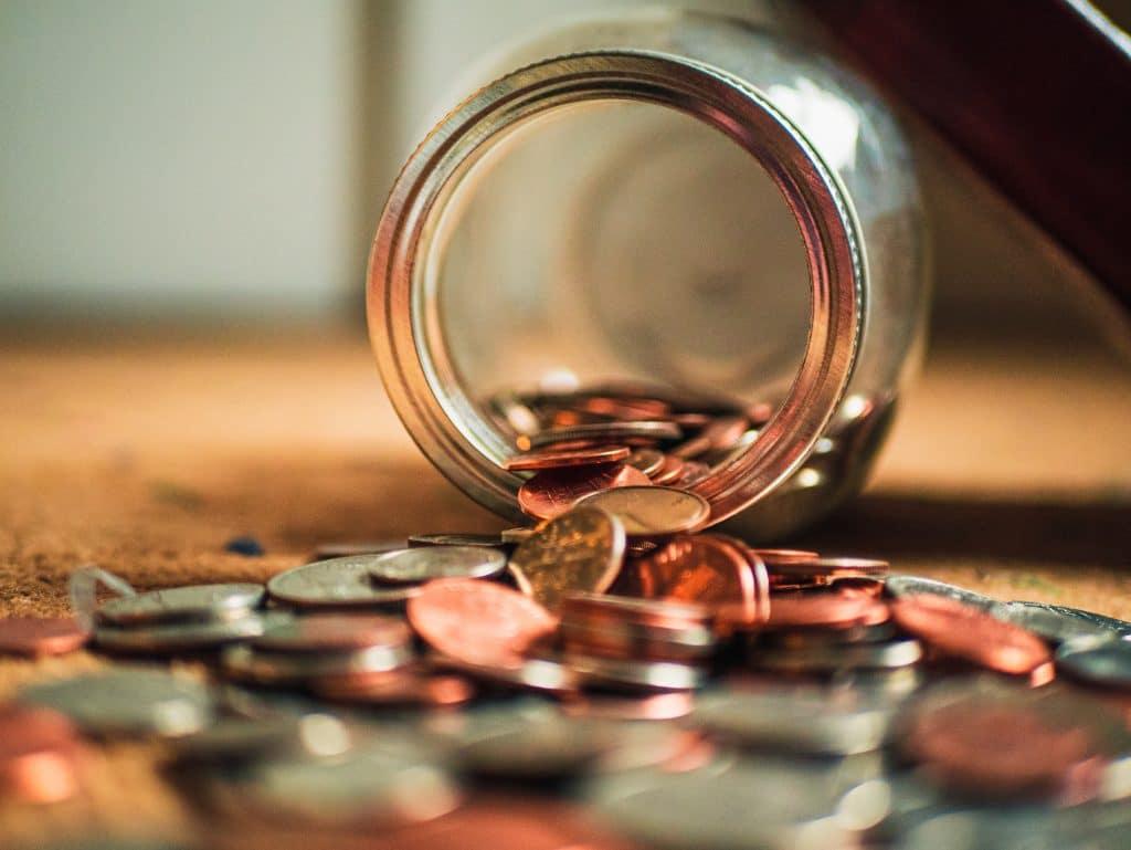 Bild von Münzen, welche in und vor einem umgekippten Marmeladenglas