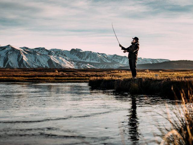Ein Fliegenfischer alleine am Ufer eines Sees mit Bergen im Hintergund