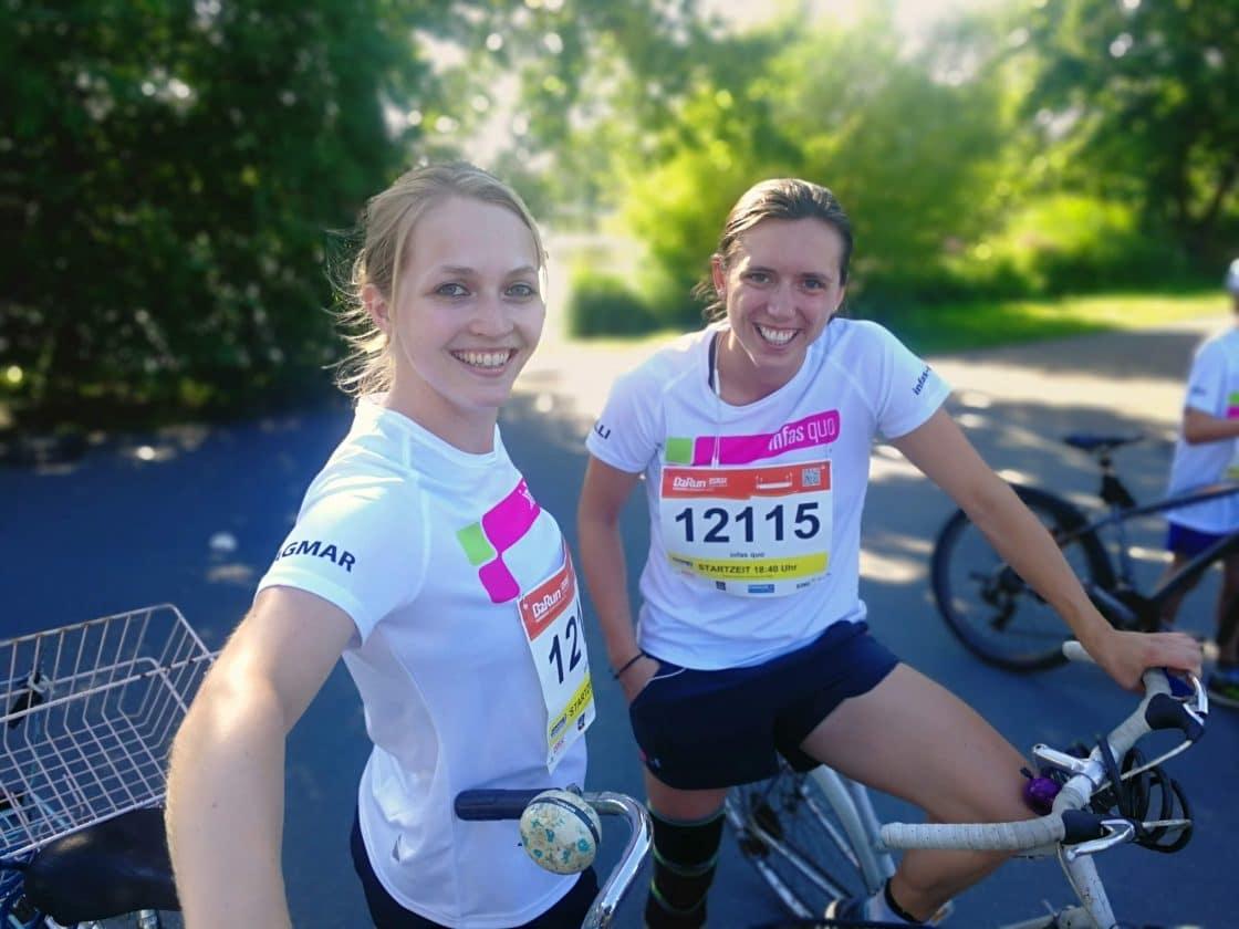 Zwei Kolleginnen im Trikot lächeln in die Kamera und warten bei ihren Fahrrädern auf den Lauf.