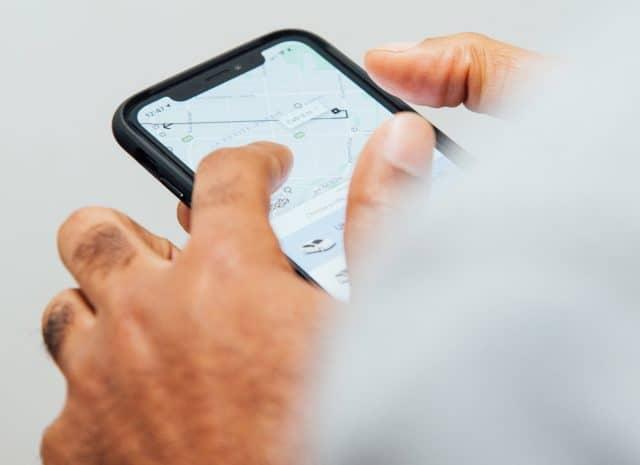 Mann hält ein Smartphone und navigiert mit einer Karte seinen Weg