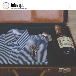 Bild eines geöffneten Koffers, welcher ein gestreiftes Hemd, eine Uhr, sowie ein Hennessy Cognac mit zwei kleinen Metallgläsern beinhaltet