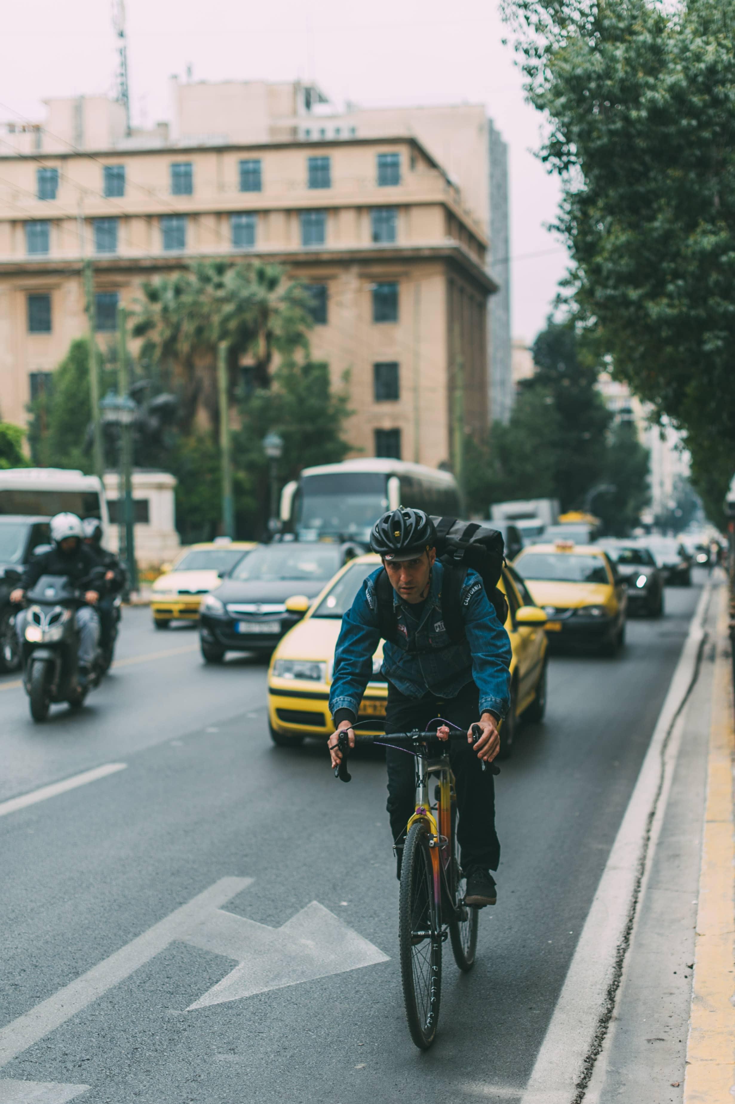 Verkehrsreiche Sraße in einer Stadt, ein Fahrradfahrer mit Helm im Vordergrund