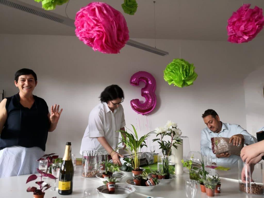 Mitarbeiter pflanzen gemeinsam kleine Topfpflanzen in Gläser