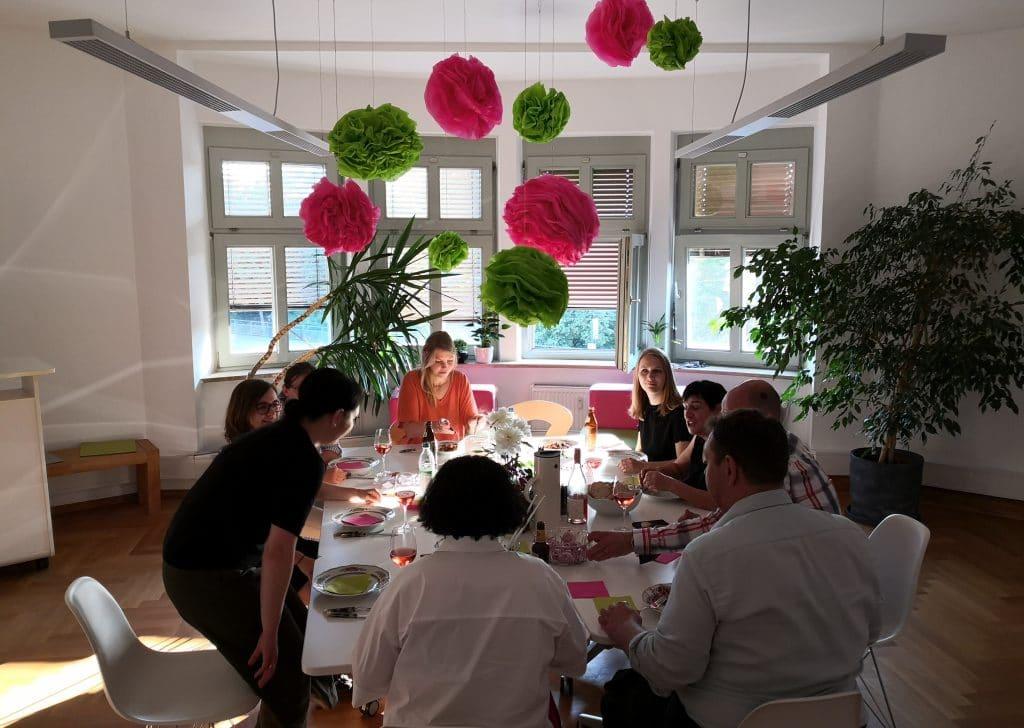 Mitarbeiter sitzen und essen um einen Tisch in einem geschmückten Raum